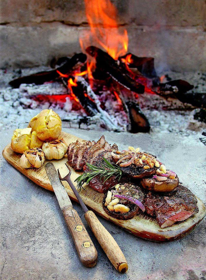roasting over an open fire... roast meat, garlic and mushrooms with baked potatoes