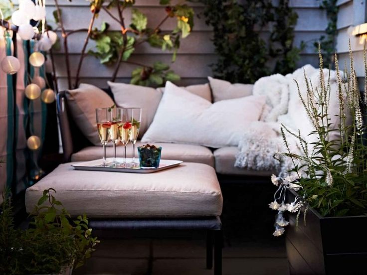 romantische Atmosphäre - Outdoor Möbeln mit Polsterkissen, Pflanzen und angenehme Beleuchtung