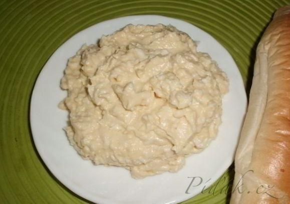 POTŘEBNÉ PŘÍSADY:  2 natvrdo vařená vejce  50 g rostlinného másla  100 g smetanového taveného sýra  3–4 stroužky česneku  citrónová šťáva  sůl  pažitka  POSTUP PŘÍPRAVY: Sýr rozetřeme s tukem, přidáme jemně nastrouhaná vejce, česnek rozetřený se soli, trochu citrónové šťávy a vše důkladně promícháme.