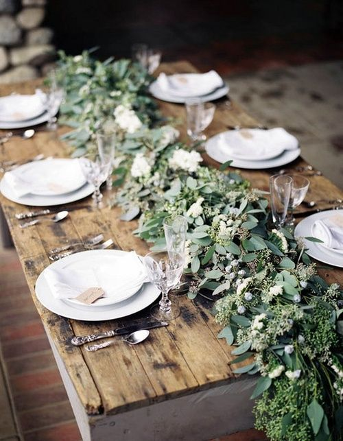 Rustic wedding table setting idea with a centrepiece of nature and/or florals and the use of wood which is a specific element of rustic country aesthetic.