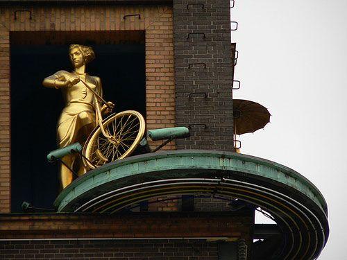Vejrpige med cykel. På hjørnet af Københavns Rådhusplads (og Vesterbrogade) står en bygning med et tårn. Bygningen hedder Richshuset og er fra 1936. På tårnet er et termometer der fortæller om det idag er koldt eller varmt. Men et termomenter kan ikke fortælle os hvordan vejret er. Derfor har kunstneren Ejnar Utzon Frank formet to skulpturer der på skift kommer frem oppe i tårnets top. Når det regner, kommer pigen med regnfrakken og paraplyen frem – hun skal ud og lufte sin hund. Når solen…