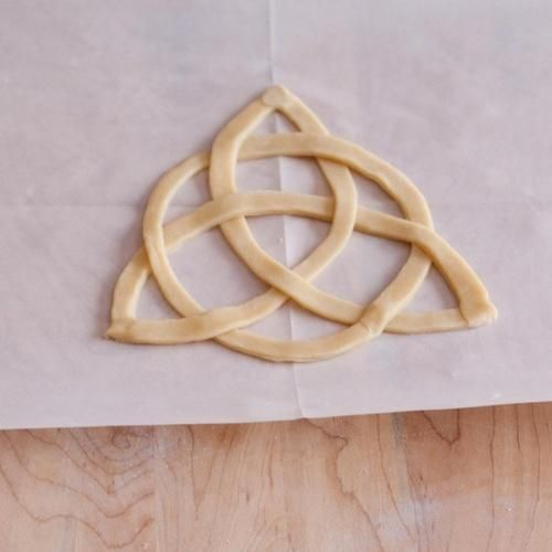 You will also need parchment paper and a printed image of the Celtic knot you would like to create. Follow a good recipe for basic pie dough. Then cut out curved strips of pie dough to about a 1/2 inch wide and 10 to 12 inches long. See More: Quick, One-Pot Meal Ideas To Feed the Whole Family Place a