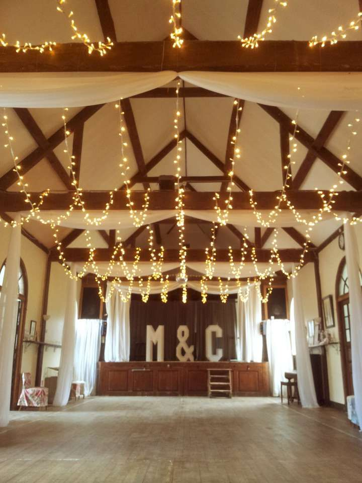 Wedding lights in a village hall, fairy light canopy and curtain drapes for a total transformation. Letters by Doris Loves. Lights and drapes by Oakwood Events.