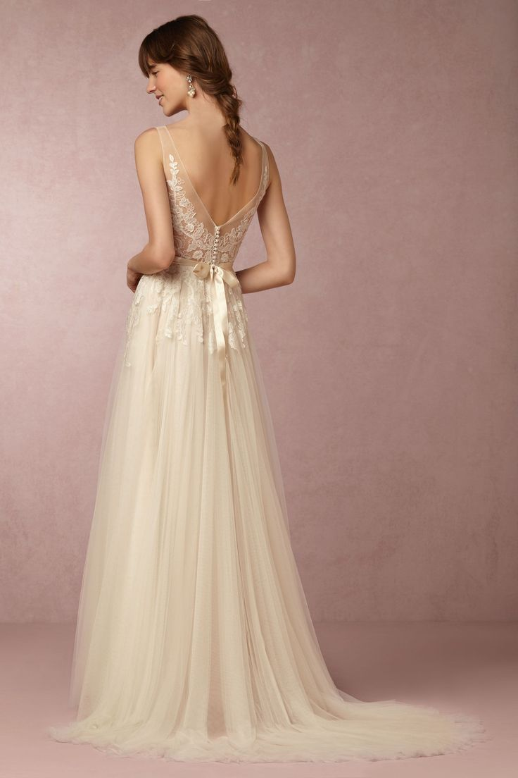Feminine, airy, and utterly romantic, this Watters wedding dress is hard to resist. Floral lace blooms from its delicate illusion neckline, through a fitted bodice, and into a frothy tulle skirt. A sheer back, lined with femme pearl buttons, and a soft blush lining provide the finishing touches. | Reagan Gown from BHLDN