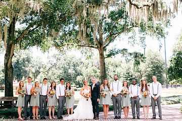 the wedding party pauses under the oaks after the ceremony. Bridesmaids in pale mint green dresses and groomsmen in grey slacks, bow ties suspenders.