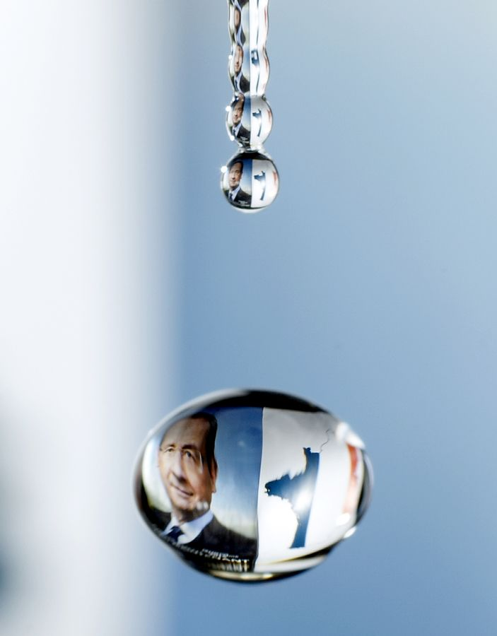 A drop of water reflects the campaign poster of newly elected president Francois Hollande and a map of France emblazoned with the colours of the French flag. (Getty Images)