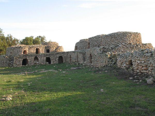 """A Tazota Moundib, un ensemble unique, composé de 7 tazotas regroupées dans un seul enclos, daté de 1922 (inscription gravée sur un linteau de porte dans la maison de maître). Cinq de ces tazotas servaient de grange ou de grenier, rassemblées en un seul tenant, et deux autres, à quelques mètres d'elles, servaient d'étable : le toit est recouvert d'une pierre que l'on peut basculer pour l'aération du local. Avec, le long de l'enclos en pierre sèche, des """"mangeoires"""" ou des abris."""