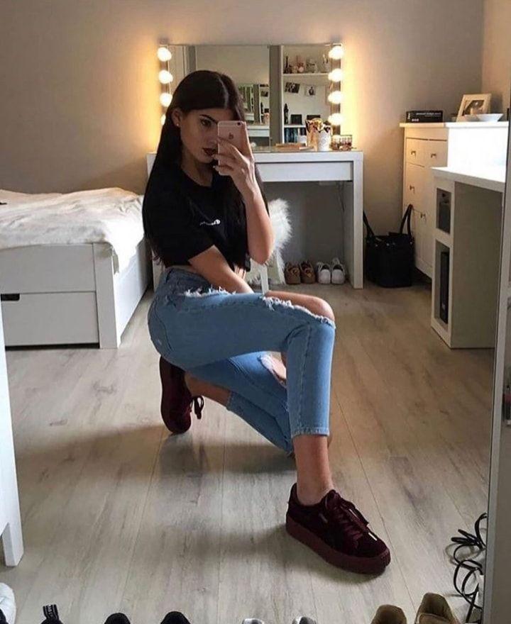 Mujer tomandose una selfie frente a un espejo y atrás se muestra parte de su cuarto y una mesa con espejo de luces