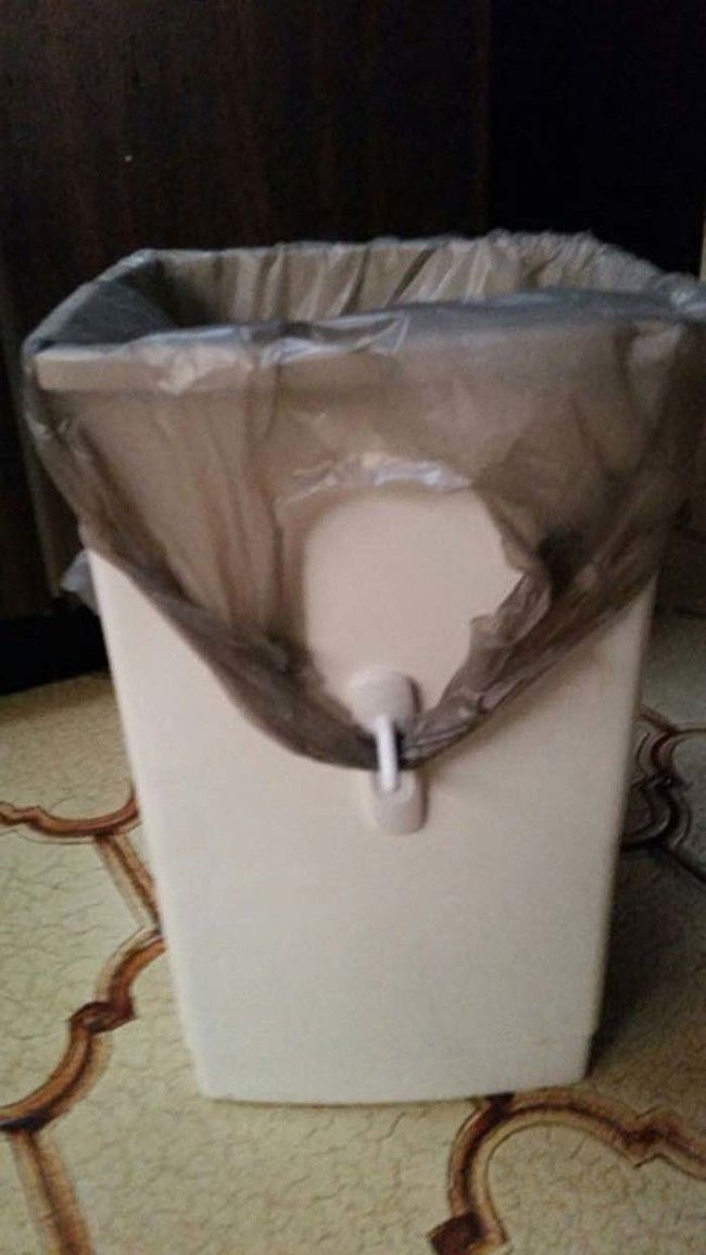 GENIUS! If you use grocery bags as trash bags in small garbage bins, here's how to keep the handles from flying around: