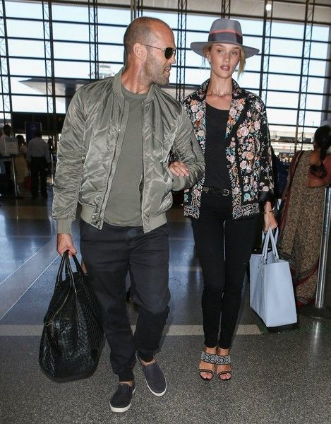 The jet-setting duo rocked their airport outfits with Huntington-Whiteley wearing a loose floral blazer and black skinny jeans while being led by Statham in an olive green bomber and matching tee.