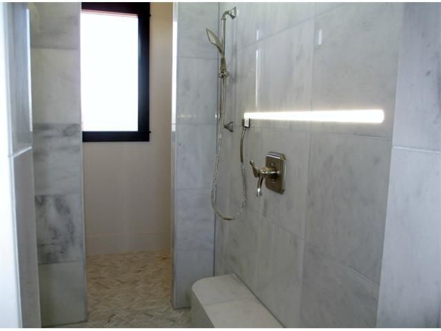 Amazing master spa that includes an open double shower with white marble and sitting area 8100 Magnolia Ridge Cv, Austin TX 78738