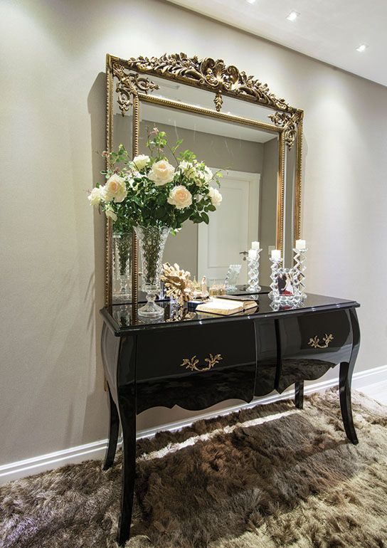 O espelho clássico apoiado sobre o aparador em laca preta e o tapete na cor fendi configuram o hall da área íntima. Vaso e castiçais em cristal completam a composição.