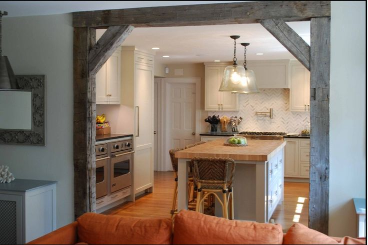 rustic beams in kitchen remodel to open up kitchen. hmmm. maybe something we can add to the big openings to the dining room.