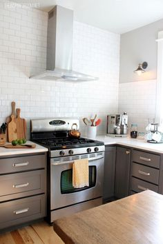 Kitchen Reno - Gray bottom cabinets, white upper cabinets, and daltile white subway tile