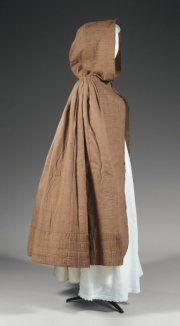 Enveloppe pour l'hiver, Provence, début du XIXème siècle. Grande cape à capuchon en coton imprimé au rouleau de cuivre d'un motif vermiculé blanc sur fond puce, large bande plissée ou « polonaise » courant sur les bords et le pourtour de la capuche, doublure de laine grattée (très bel état)