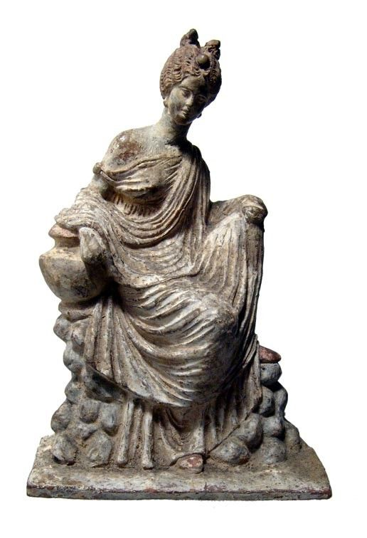 Tanagra figure of a seated woman, 3rd-2nd century B.C. Her hair up in plaits into a double chignon, she sits contemplatively on rocky platform, resting right elbow on a vase beside her, her left hand draped over her left knee, her chiton slips slightly from her right shoulder and her shawl hangs loosely around her, traces of original pigment over the white dressing, 17 cm high. Private collection