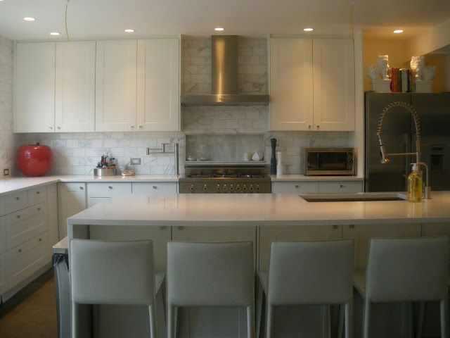 Designer Erica Cook's kitchen. Love the white cabinets with white counters, the marble subway tiles and niche above the cooktop.