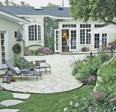 Soften with Curving Lines  Sometimes a problem can be turned into an asset. Rugged terrain determined the gracious, curved shape of this patio. It is easily accessible from the house through French doors. Large windows allow views of the patio to be enjoyed from indoor spaces as well. Lush plantings follow the curves, creating a quiet garden escape.