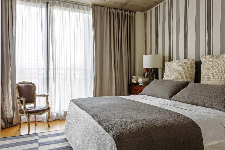Dormitorio en tonos neutros con doble cortinado –voile translúcido detrás y lino por delante– y un género pintado a mano en la pared de la cabecera. Ropa de cama de Restoration Hardware y mesa de luz heredada con lámpara rústica (Iluminación Agüero).