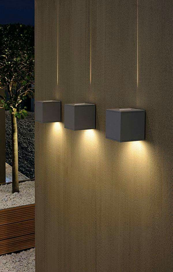 Dual Cube Lighting: A chunky square exterior wall light fitting with narrow glass diffuser slot to the top and broad circular glass diffuser to the base, creating an interesting and decorative fine light beam upwards with a functional wider beam below. Available in silver grey or white.