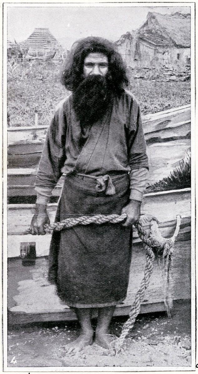 Portrait an Ainu man, a fisherman, standing beside a boat,