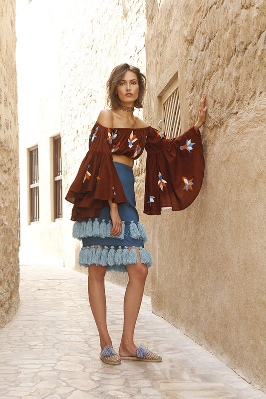 Pom pom adorned knit bombers, wool shag espadrilles and tassel trimmed everything?! Mochi designer Ayah Tabari, once again, is speaking my language with her spring collection. This season, the Palestinian designer has moved on from the motifs of Uzbekistan and onto the warm desert hues and pops of