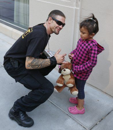"""Leland Chapman, a cast member of """"Dog The Bounty Hunter"""" takes a picture with 3-year-old Tatiana Castilleja in front of the Ambassador Hotel. (May 7, 2013)"""