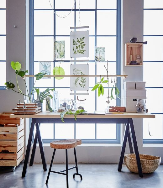 "A desk in front of a window is decorated with botanical elements.  ""These stackable KNAGGLIG boxes provide storage, while the rod hanging in the window is great for hanging things from hooks."""