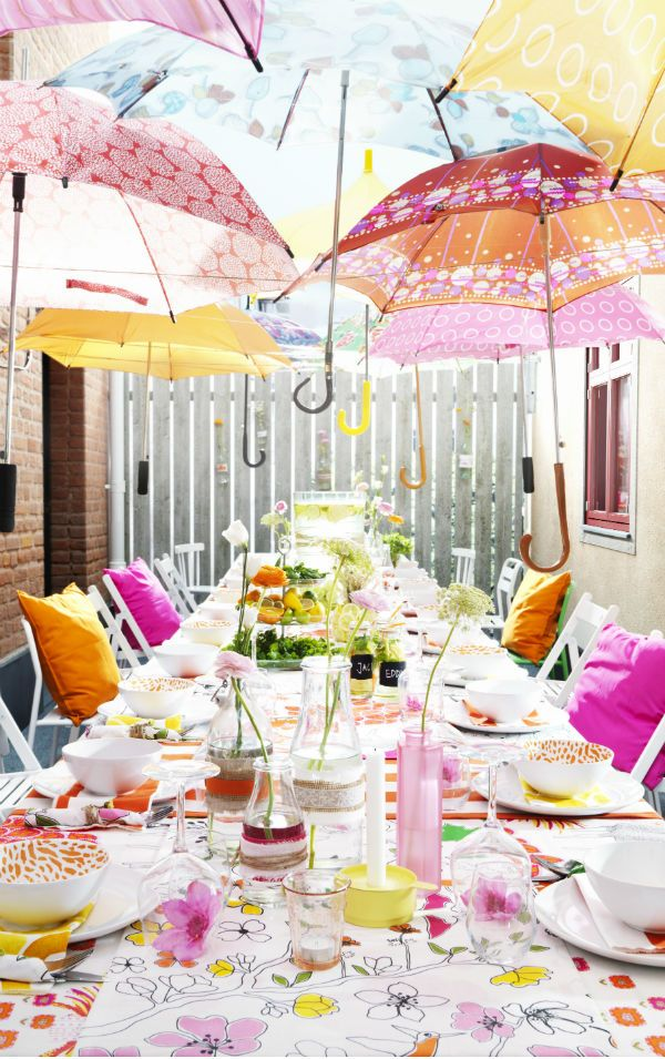 Create a fun canopy of umbrellas and mix and match fabric and serving ware in bright, fun colors for an outdoor party that's sure to welcome the season | @covercouch