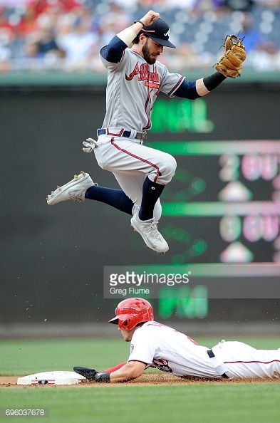 News Photo : Dansby Swanson of the Atlanta Braves jumps over...