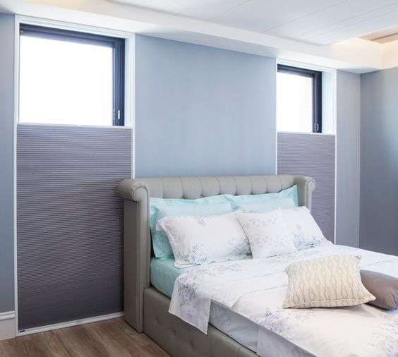 Neutral honeycomb blinds fit perfectly into this tranquil bedroom.