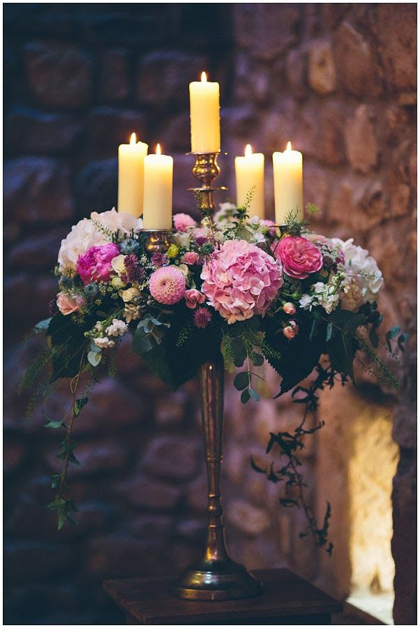 The Baroque Candelabras are perfect for framing the ceremony here at Browsholme Hall the chunky pillar candles and full voluptuous floral design are strong, bold and full enough to stand out against the stone back drop