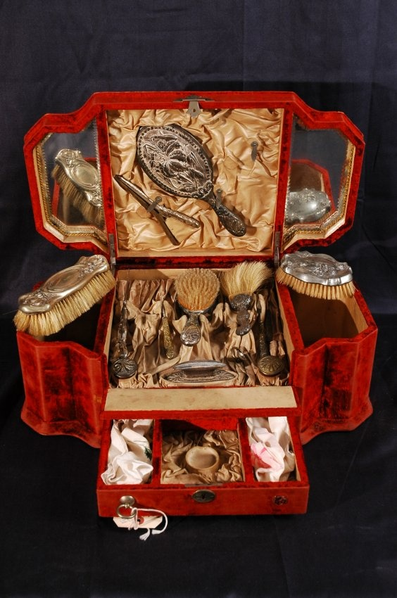 Antique French dressing kit encased in red velvet carrying case.  13 pieces includes brush, mirror, perfume jar, filer, and more.  20 x 12 x 11.