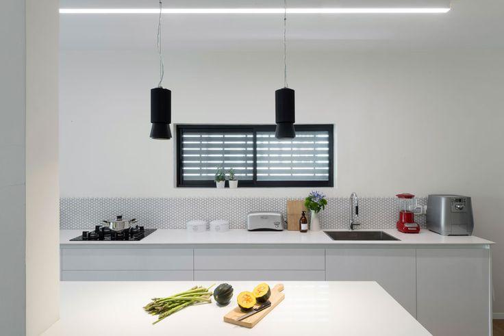 הם ביקשו לשפץ את הדירה בסגנון מודרני, שלא יהיה קר מדי. בין המטבח הפתוח לסלון יש עמוד, שבצדו האחד אי עבודה, ומצדו השני שולחן האוכל (צילום: גדעון לוין)
