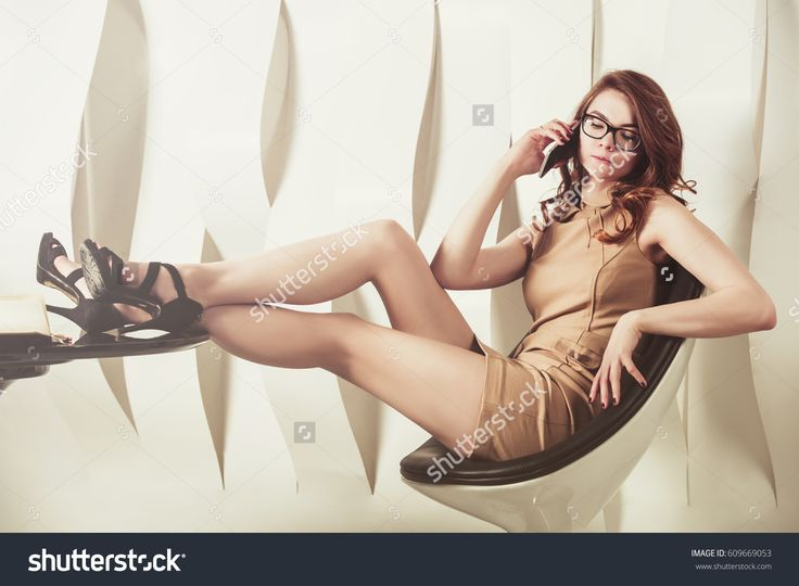 A beautiful businesswoman talking on phone while her legs on a table