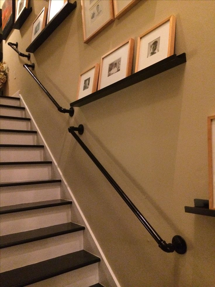 """Finished product. DIY railing for stairs using 1"""" pipe, elbow joints, 3"""" nipples and metal flanges mounted directly to wall. All spray painted with a black primer and high-gloss black spray paint."""