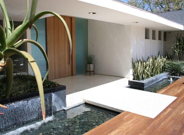 A modern take on the moat: entryway over water. Mixed wood panels against a crisp white entrance and dark planters. Orange Street Studio, Skytop project in Encino, California. We love their modern aesthetic.