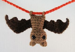 "This tiny little bat, depending on the yarn you use, will end up about 2"" tall, with a wingspan of about 5"". The feet are actually small loops, so your bat can hang upside down from a small stick or length of yarn or cord."