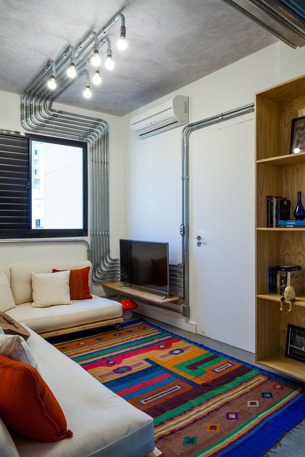 Apartamento pequeno com ideias econômicas. Na sala, as instalações aparentes dão um ar industrial, enquanto que o tapete colorido alegra o ambiente.