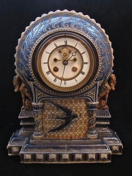 """Martin Brothers Clock decorated with a Swallow and Flanked by Two Grotesque Dragons. The clock movement having been cleaned and conserved and by the Fine French Clock Maker Samuel Marti. The body of the clock with firing cracks. Dated: 1879 Dimensions: 12.00"""" high x 10.00"""" wide x 5.00"""" deep"""
