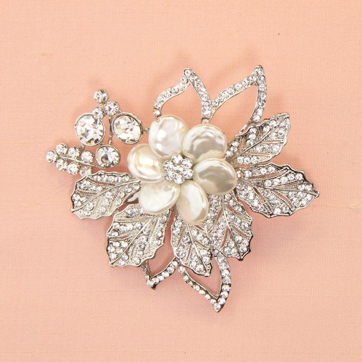 Pearlised flower with diamante leaves set on a clip. Measurement: 8.5 cm long x 7 cm wide.This piece is presented in Roman