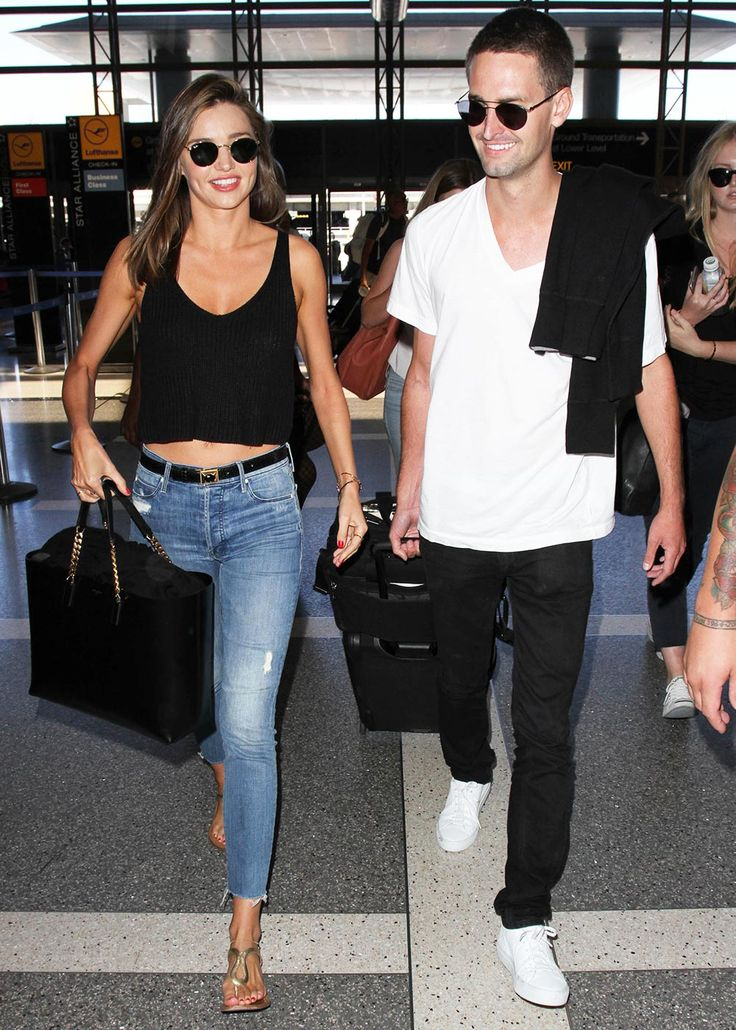 Miranda Kerr mastered casual summer style as she made her way through LAX airport with new boyfriend Evan Spiegel, teaming skinny jeans with a knitted crop top and metallic sandals - August 12, 2015