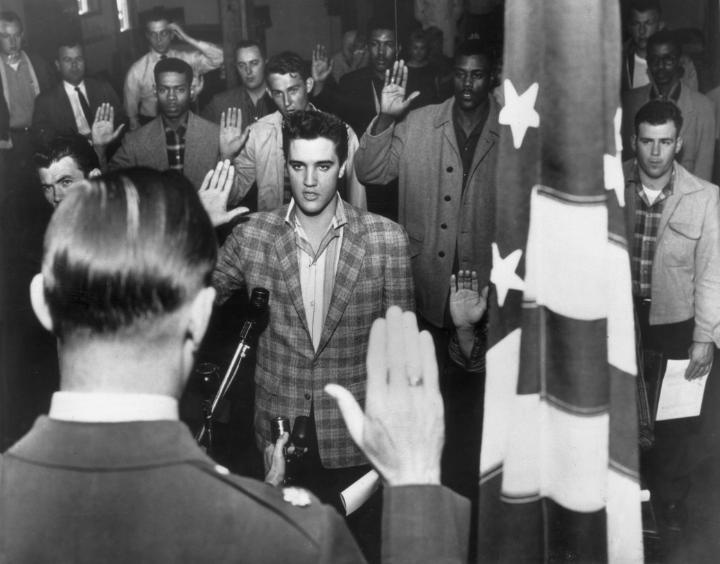 Elvis stands with a group of young men at an induction center, raising their right hands as they are sworn into the United States Army by an offier standing next to the American flag.
