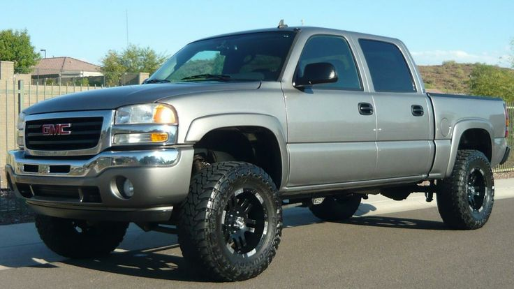 lifted 2014 Silver GMC Sierra truck with nice wheels