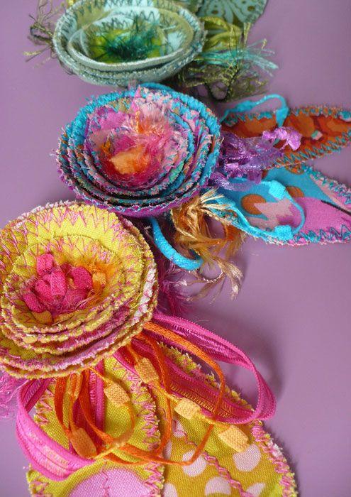 Spille con spirali di fiori in tessuto stampato fantasia, passamanerie e filati.       E zig-zag in ogni dove.