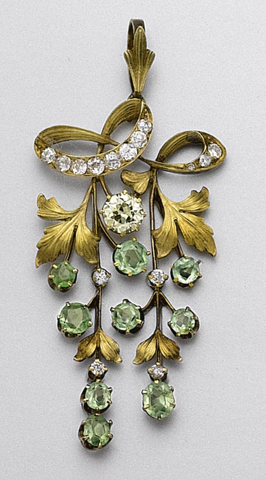 GOLD, DEMANTOID GARNET AND DIAMOND GRAPE CLUSTER, RUSSIAN, EARLY 20TH CENTURY. The articulated motif decorated with 9 round and cushion-shaped demantoid garnets representing grapes, further accented with 1 old European-cut diamond of yellow tint and 15 small old European-cut diamonds, Russian assay marks.
