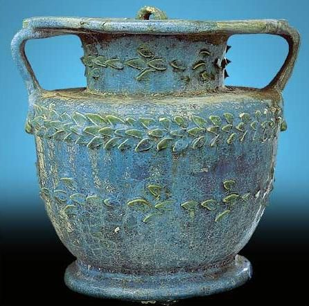*TWO HANDLED VASE:  Material: Blue Faience.  Period: Roman Period (Early 1st or 2nd Century AD)  In Egypt, faience production was a major craft industry, + there a multitude of different objects made from this glass-like material throughout Egyptian history. However, the style of this specific piece makes dating it all but impossible, though it can be placed w/in the early common era.