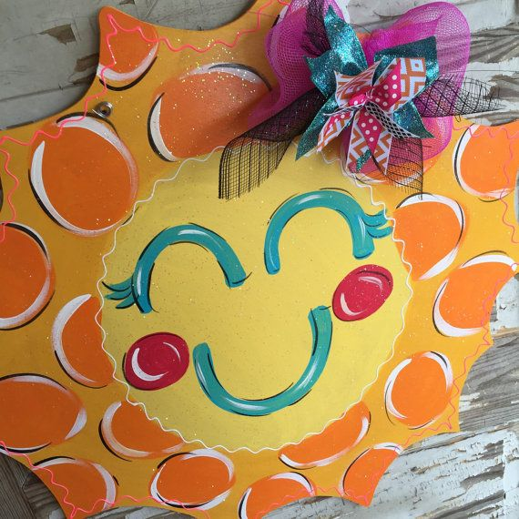 This sunshine door hanger is a huge summer hit! It will make you smile day in and day out while it adorns your door! It is hand-cut out of 1/4 inch pretreated wood, painted with acrylic paint, and finished with a protective clear coating that prevents chipping, peeling, or fading. It hangs from sturdy metal wire, and it is accessorized with a multi-layered deco mesh bow and ribbon bow.