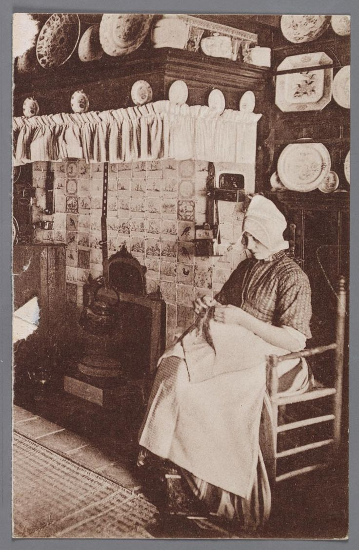 Interieur Hotel Spaander - Volendam. 1920-1930 Volendamse vrouw in dracht bij een betegelde haard bezig met handwerk. #NoordHolland #Volendam