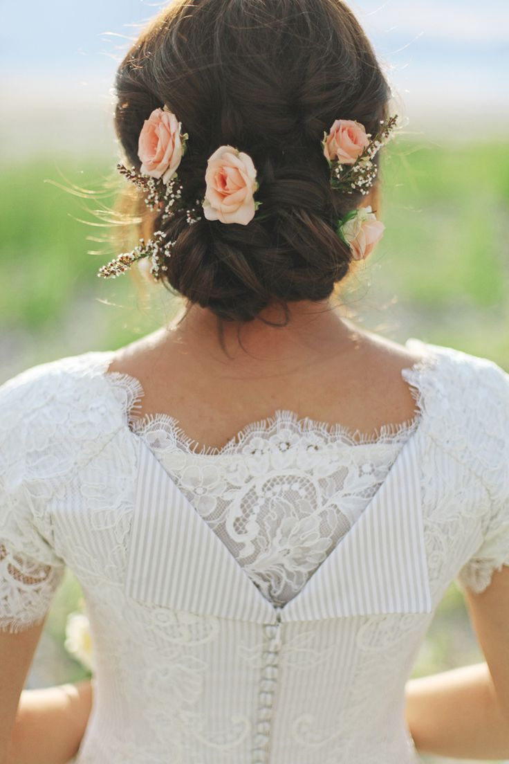 low twisted wedding updo with peach flowers and a veil